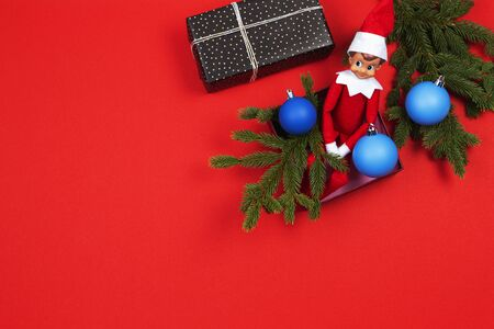 Christmas background. Red toy Santa elf sitting in present box with green fir branches and decoration baubles on red background. Top view Reklamní fotografie - 133483836