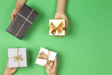 Hands holding presents wrapped in gift paper on light green background. Christmas, New Year, holidays concept 版權商用圖片
