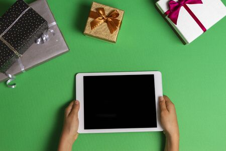 Top view to kid hands with tablet computer and Christmas present boxes on light green background