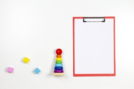 Colorful baby kid toys and red clipboard with blank sheet of paper on white background. Top view