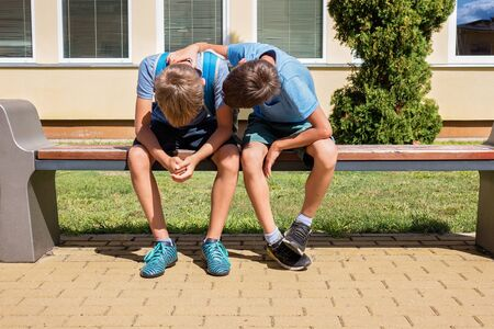 Kid comforting consoling upset sad boy in school yard Stock Photo