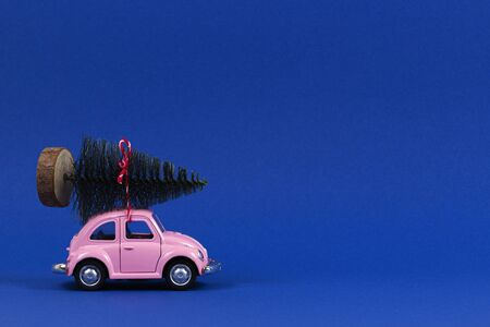 Vilnius, Lithuania - November 15, 2019: Little retro pink toy car with Christmas tree