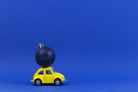 Vilnius, Lithuania - November 15, 2019: Yellow retro toy model car with small navy Christmas tree decoration bauble on blue background