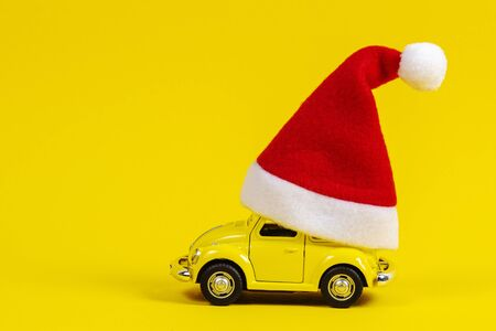 Christmas background. Little retro toy model car with small red Christmas Santa Claus hat on yellow background