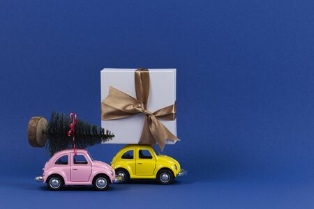 Little retro toy model cars with present gift box and small Christmas tree on navy blue background