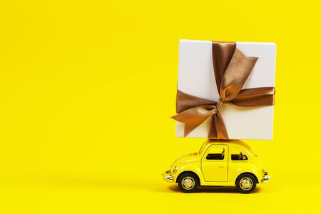 Vilnius, Lithuania - November 15, 2019: Little retro toy model car with present gift box on yellow background.