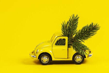Christmas background. Little retro toy model car with small Christmas tree branch on yellow background
