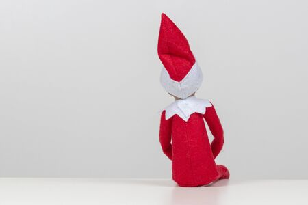 Back view to little toy Christmas Santa elf sitting on white background 版權商用圖片
