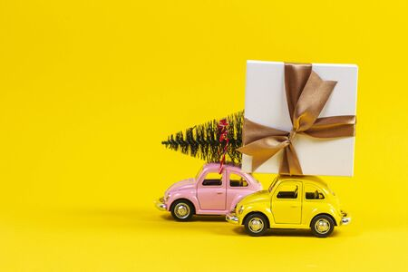 Vilnius, Lithuania - November 17, 2019: Little retro toy model cars with present gift box and small Christmas tree on yellow background.