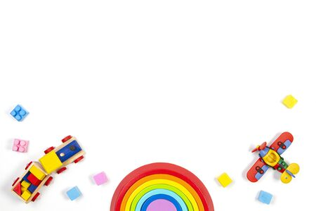 Baby kids toys background with wooden train, rainbow, plane and colorful blocks. Top view, flat lay