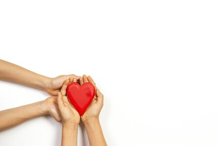 Adult and child hands holding red heart over white background. Love, healthcare, family, insurance, donation concept Stockfoto - 134568659