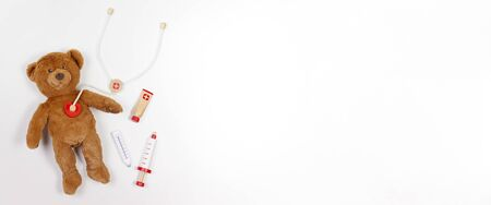 Teddy bear with toy stethoscope and toy medicine tools on white background. Top view. Copy space for text