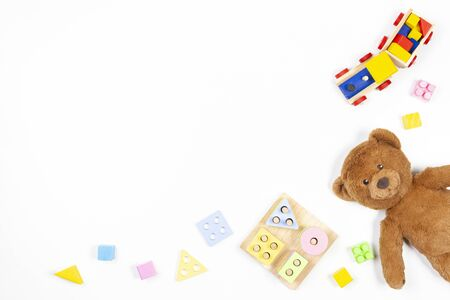Baby kids toys background. Wooden educational geometric stacking blocks shape color recognition puzzle toy, wooden train, teddy bear and colorful blocks on white background. Top view, flat lay Stockfoto - 134568668