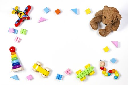 Baby kids toys frame with teddy bear, wooden toys and colorful blocks on white background. Top view, flat lay. Copy space for text