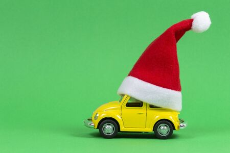 Vilnius, Lithuania - November 16, 2019: Christmas background. Little yellow retro toy model car with small red Christmas Santa Claus hat on green background