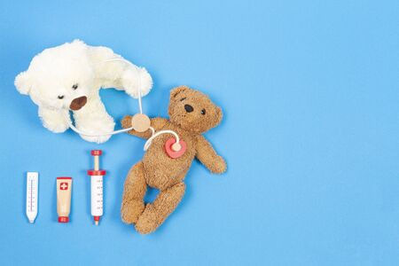 Teddy bear doctor with stethoscope and teddy bear patient on light blue background with wooden toy medicine tools