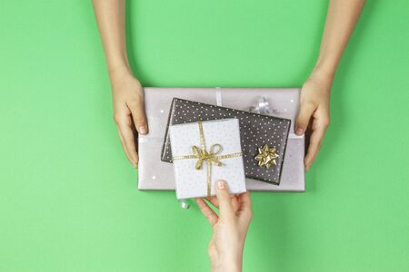 Hands give and take presents boxes over light green background. Christmas, New Year, holidays, birthday concept Stockfoto - 134568694