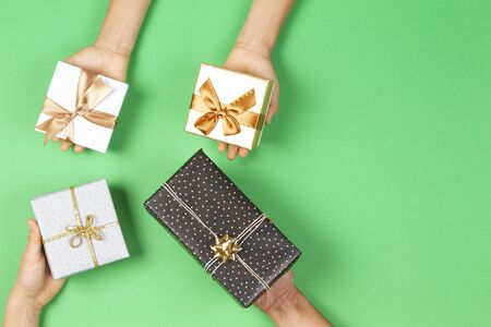 Hands holding presents wrapped in gift paper on light green background. Christmas, New Year, holidays concept Stockfoto