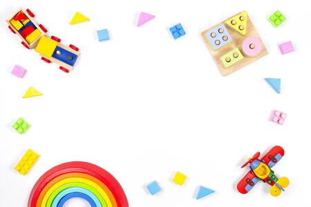Baby kids toys background. Wooden educational geometric stacking blocks toy, wooden train, rainbow, airplane and colorful blocks on white background. Top view, flat lay Stockfoto