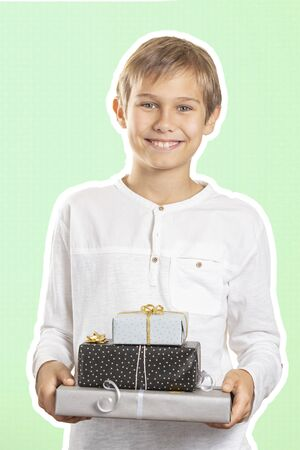Happy boy holding stack paper wrapped present gift boxes. Magazine collage style with light green color background. Holidays, Christmas concept Stockfoto - 134568716
