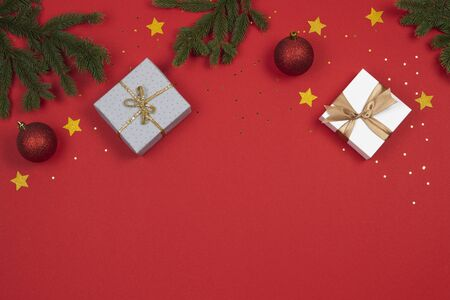 Christmas background. Green fir tree branches, present boxes, decoration bauble balls and golden glitter stars on red background Stockfoto