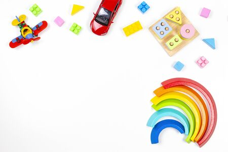 Baby kids toys background. Wooden educational geometric stacking blocks toy, rainbow, airplane, car and colorful blocks on white background. Top view, flat lay