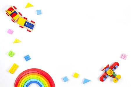 Baby kids toys background. Wooden train, constructor airplane, stacking toy rainbow, plane and colorful blocks on white background. Top view, flat lay Stockfoto