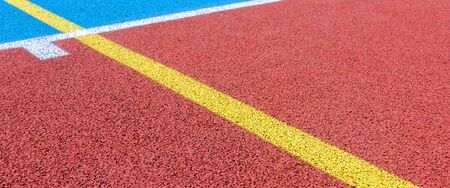 Colorful sports court background. Top view to red and blue field rubber ground with white and yellow lines outdoors.
