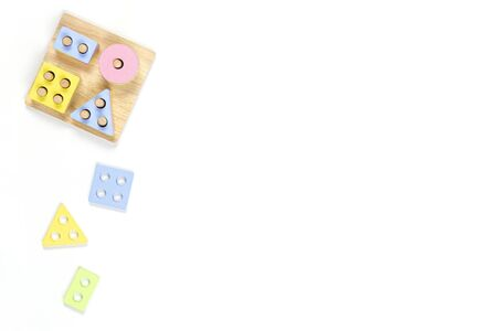 Wooden pastel color geometry educational toy for children on white background. Educational shape color recognition puzzle stacker. Early childhood development puzzle toys