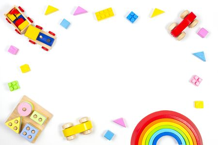 Baby kids toys background. Wooden educational geometric stacking blocks toy, wooden train, rainbow, plane and colorful blocks on white background. Top view Stockfoto - 134568727
