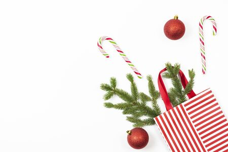 Christmas present gift bag with fir tree branch, candy canes and Xmas decoaration bauble on white background. Stockfoto - 134568726