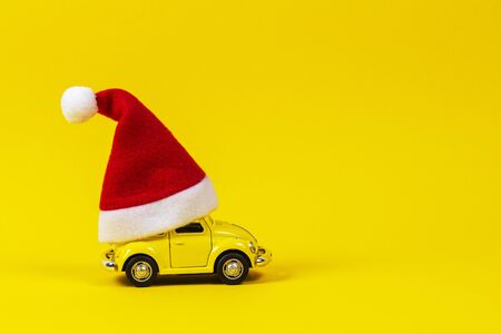Vilnius, Lithuania - November 16, 2019: Little retro toy model car with small red Christmas Santa Claus hat on yellow background Redakční