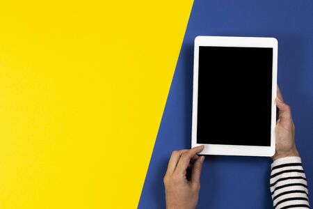 Female hands with digital tablet computer on navy blue and yellow background. Top view