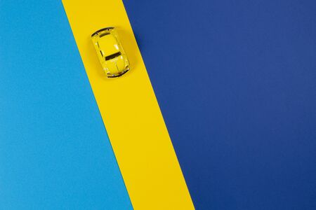 Vilnius, Lithuania - December 6, 2019: Small yellow retro toy car on yellow and blue background. Top view