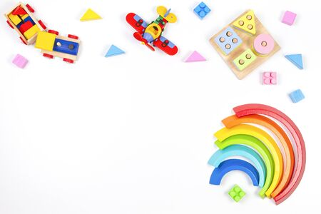 Baby kids toys background. Wooden educational geometric stacking blocks toy, rainbow, airplane, train and colorful blocks on white background. Top view Stock Photo