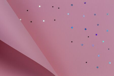 Pastel pink paper in geometric shape with glitter stars. Abstract Christmas, New year, festive background