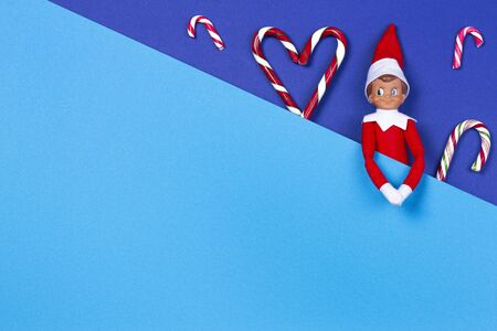 Christmas background. Little toy Santa elf and candy canes on navy blue and light blue background. Top view Reklamní fotografie