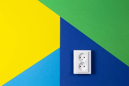 White electrical socket on geometric yellow green blue navy color background Reklamní fotografie