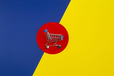 Mini shopping trolley cart on red yellow navy blue background. Online shopping, buy, sale, discount concept