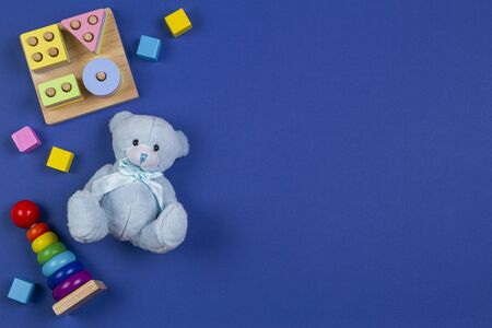 Baby kids toys background. Blue teddy bear, stacking pyramid tower, shape color recognition puzzle stacker and colorful blocks on navy blue background. Top view