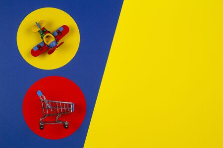 Mini shopping trolley cart and small toy airplane on red yellow navy blue background. Toys, kids, online shopping, buy, sale, discount concept
