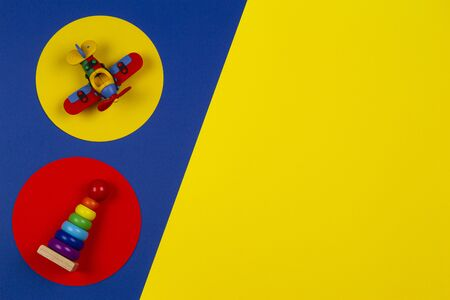 Baby kids toys background. Wooden stacking pyramid tower and red airplane on round yellow and red frames above navy blue background Stockfoto