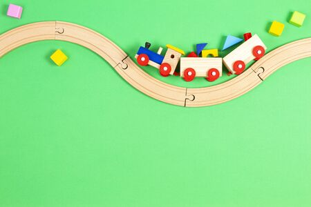 Wooden toy train with colorful blocks and wooden railway on light green background. Reklamní fotografie