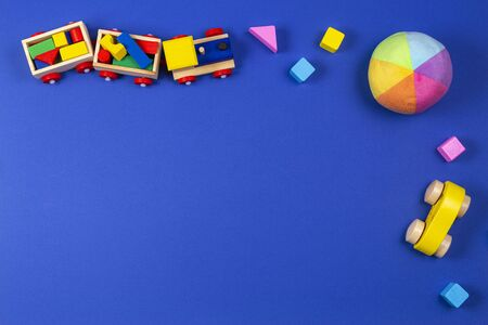 Baby kids toys background. Wooden train, wood car, colorful bricks on blue navy background. Top view, flat lay