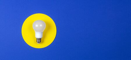 One light lamp bulb on yellow and navy blue background.