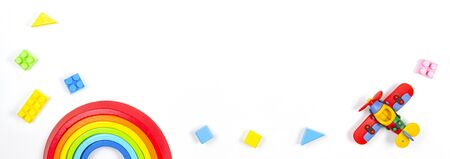 Baby kids toys banner background. Constructor airplane, stacking toy rainbow and colorful blocks on white background. Top view