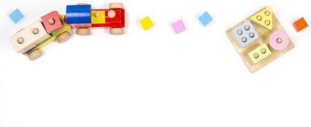 Baby kids toys background. Wooden educational geometric stacking blocks toy, wood train and colorful blocks on white background. Top view, flat lay Stockfoto
