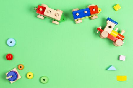 Baby kids toys background. Wooden toy train and wood stacking pyramid tower on light green background. Top view