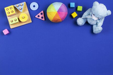 Baby kids toys background. Blue teddy bear, shape color recognition puzzle stacker, soft stuffed toy ball and colorful blocks on navy blue background. Top view