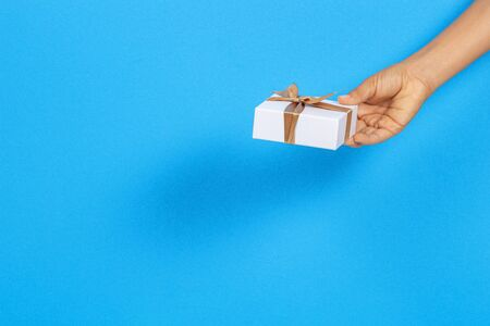 Kid hands holding white gift box with golden ribbon on light blue color background Reklamní fotografie